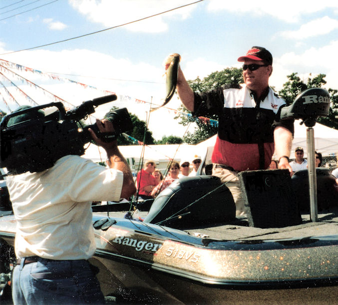 BW holds up a bass for the crowd as a cameraman shoots video of the tournament weigh-in on North and South Center Lakes in lindstrom, Minnesota